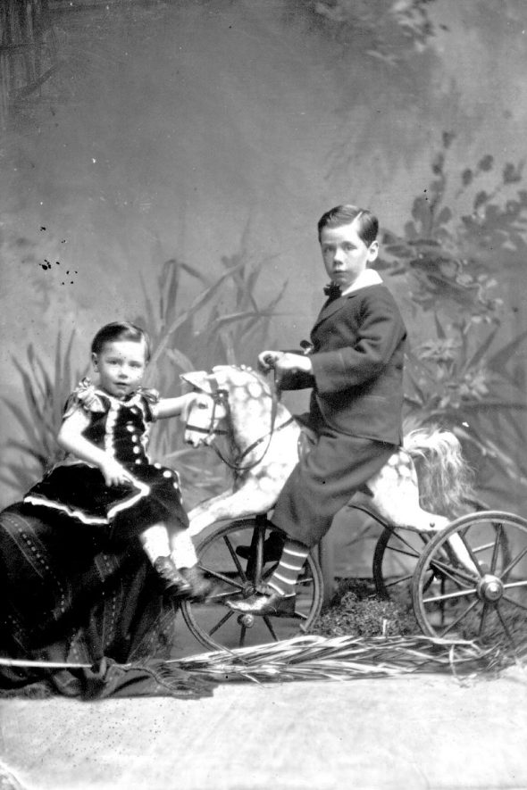 Master and Miss Gray posing with a toy horse on wheels.  1879 |  IMAGE LOCATION: (Warwickshire County Record Office) PEOPLE IN PHOTO: Gray as a surname