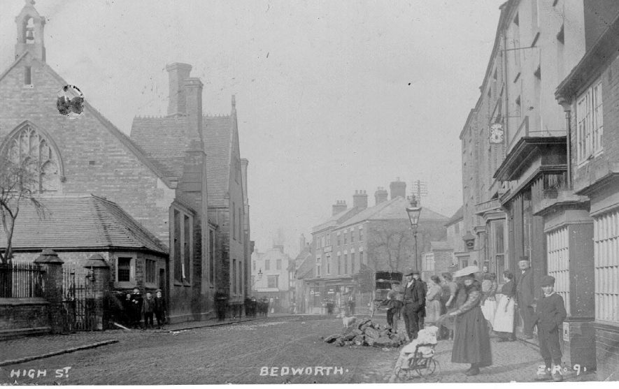 Bedworth, High Street. The building on the left is the Bedworth Central C of E school . Lady with a push chair.  1900s