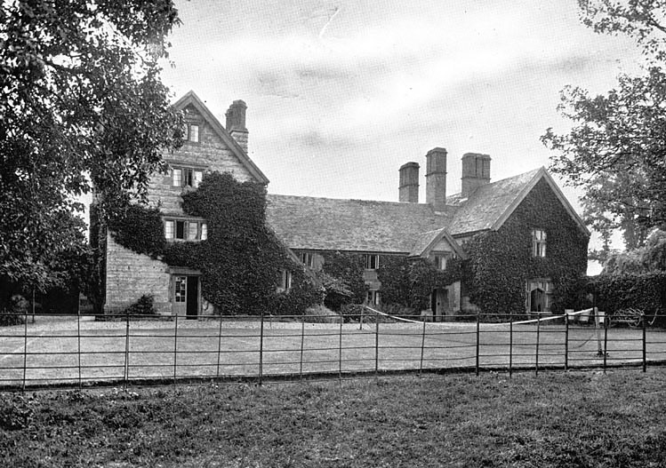 Rear view of Bickmarsh Hall, showing house with tennis lawn and deckchairs and metal seat.  1927 |  IMAGE LOCATION: (Warwickshire County Record Office)