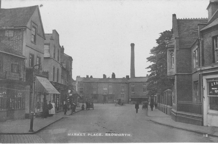 Market Place Bedworth. People standing outside shops, workers leaving factory.  1900s |  IMAGE LOCATION: (Warwickshire County Record Office)
