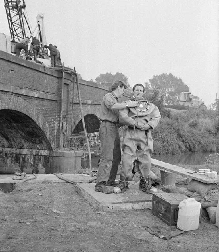Robert McCann, chief diver, helping Alan Carr prepare for a dive at the bridge repairs on the A446 road, Coleshill.  September 8th 1968. |  IMAGE LOCATION: (Warwickshire County Record Office) PEOPLE IN PHOTO: McCann, Robert, McCann as a surname, Carr, Alan, Carr as a surname