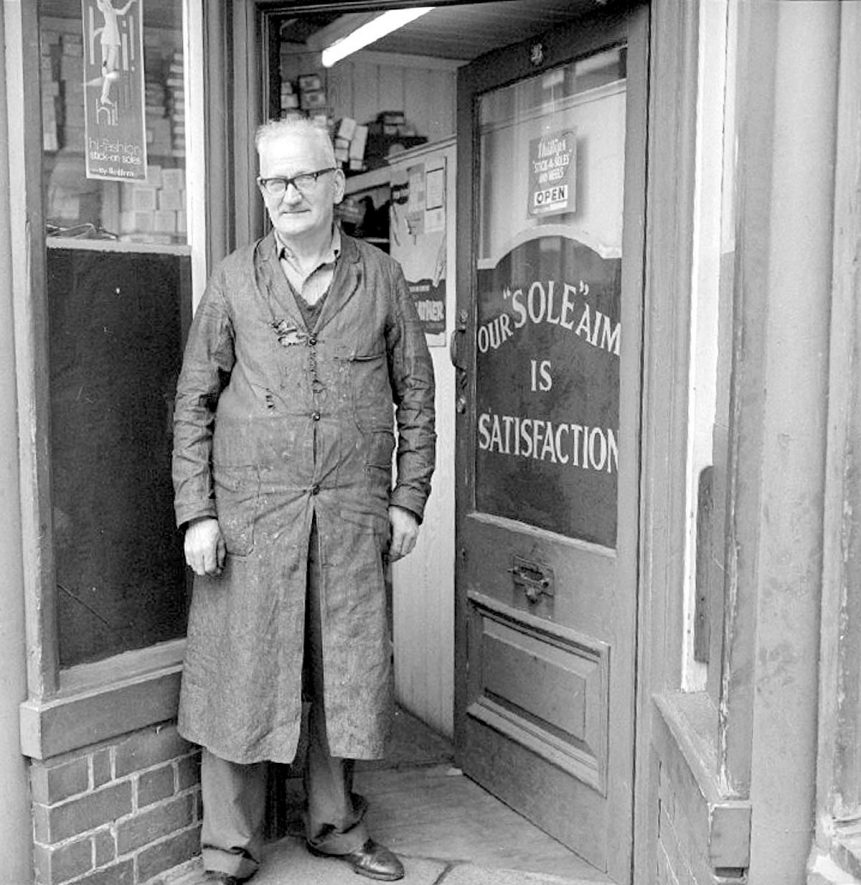 Alfred King, shoemaker standing outside his shop, owned since 1934, Nuneaton.  1969 |  IMAGE LOCATION: (Warwickshire County Record Office) PEOPLE IN PHOTO: King, Alfred, King as a surname