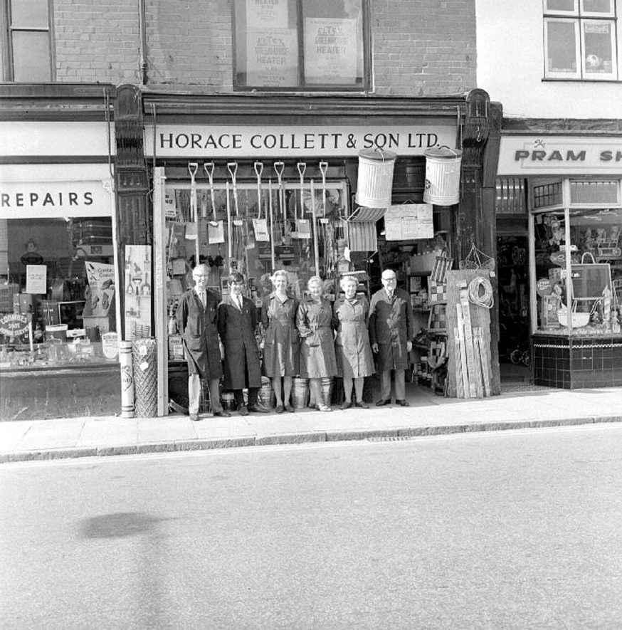 Horace Colletts, Ironmongers, Queens Road, Nuneaton.  Pictured with staff outside the shop.  Staff from left, George Randall, Graham Wright, Miss B Dawkins, Mrs Louisa Justin, Mrs Edith Collett and Ronnie Collett.  1969 |  IMAGE LOCATION: (Warwickshire County Record Office) PEOPLE IN PHOTO: Wright, Graham, Wright as a surname, Randall, George, Randall as a surname, Justin, Mrs Louisa, Justin as a surname, Dawkins, Miss B, Collett, Ronnie, Collett, Mrs Edith, Collett as a surname
