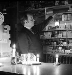 Mr Francis Reynolds working by candlelight in his off-licence in Queens Street, Nuneaton, during the miner's strike.  March 1st 1972 |  IMAGE LOCATION: (Warwickshire County Record Office) PEOPLE IN PHOTO: Reynolds, Francis, Reynolds as a surname