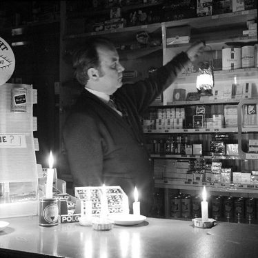 Nuneaton.  Shopkeeper working by candlelight
