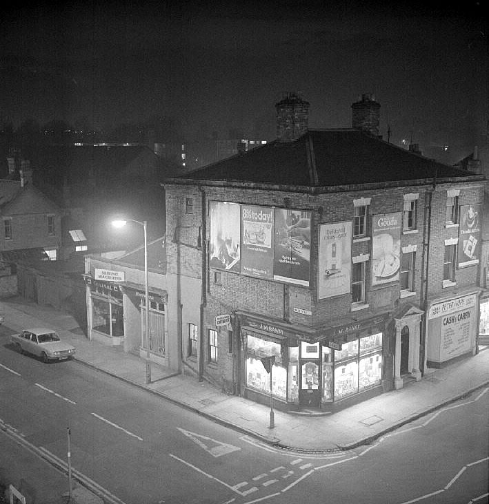 Shops at the corner of Abbey Street and High Street, Nuneaton, taken at night.  March 7th 1973 |  IMAGE LOCATION: (Warwickshire County Record Office)