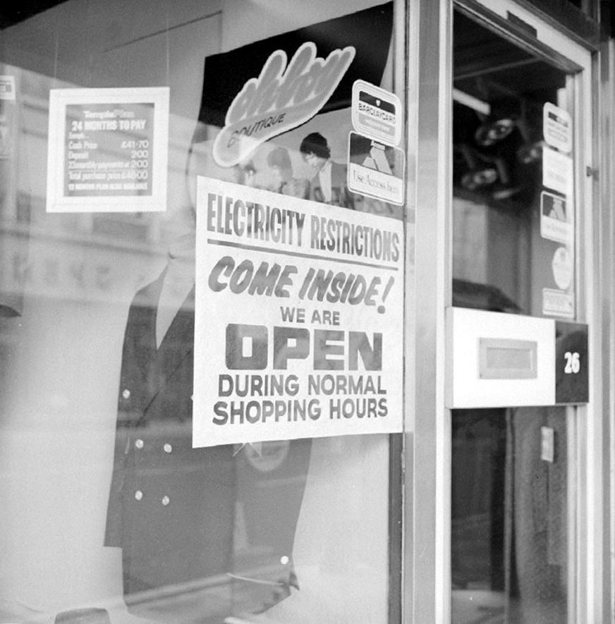 Sign in the window of John Temple's tailors shop, Market Place, Nuneaton, relating to power cuts due to the miner's ban on overtime.  January 6th 1974 |  IMAGE LOCATION: (Warwickshire County Record Office)