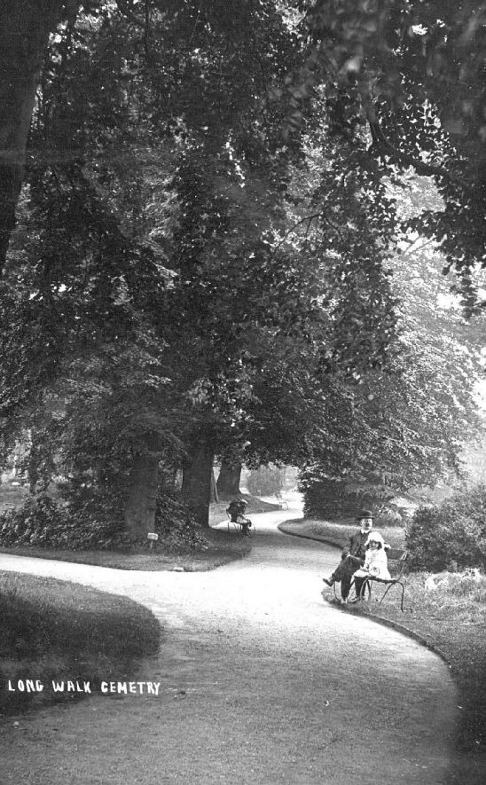 Showing the Long Walk in Bedworth cemetery with a man and a small  girl sitting on a garden seat.  1920s |  IMAGE LOCATION: (Warwickshire County Record Office)