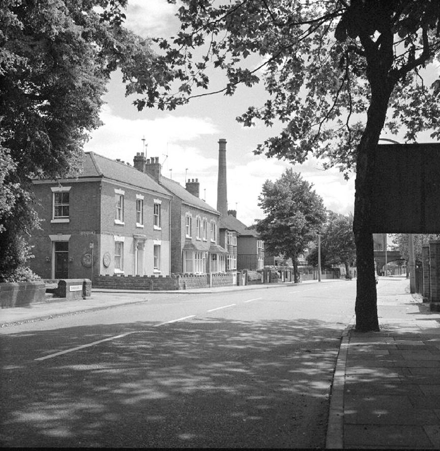 Attleborough Road with King Edward Road to the left.  Detached houses and an industrial chimney. Nuneaton.  24 June 1977 |  IMAGE LOCATION: (Warwickshire County Record Office)