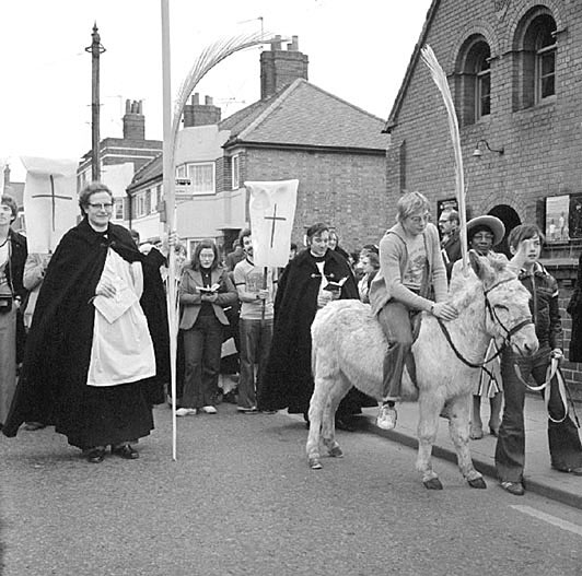 Palm Sunday procession about to move off from Edward Street Mission Church to Coton Parish Church, Nuneaton.  On left, Rev. Colin Henderson, Vicar of Coton. Behind the donkey, Rev. Tony Danby, Curate of Coton, on the donkey, Mr Colin Brown.  19 March 1978 |  IMAGE LOCATION: (Warwickshire County Record Office) PEOPLE IN PHOTO: Henderson, Revd Colin, Henderson as a surname, Danby, Revd Tony, Danby as a surname, Brown, Colin, Brown as a surname