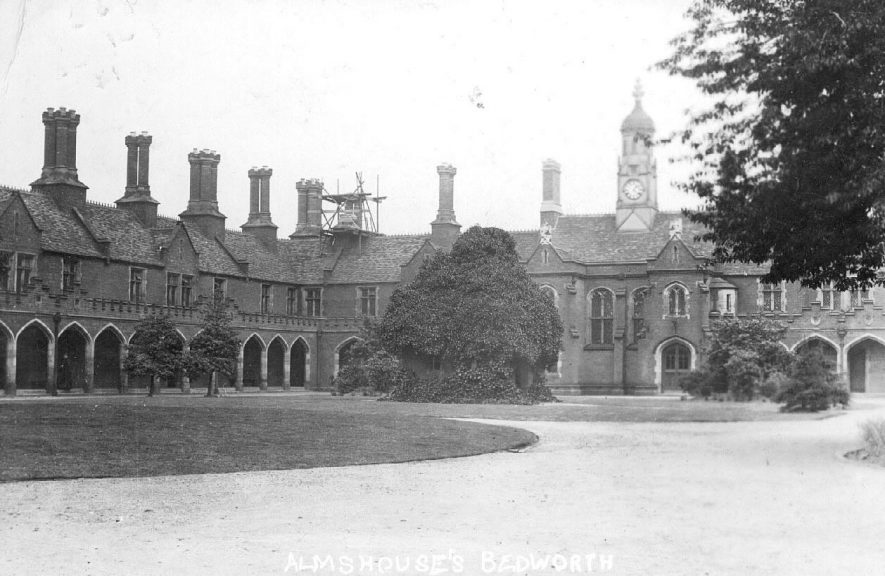 Almshouses with clocktower and tall chimneys, Bedworth.  1910s |  IMAGE LOCATION: (Warwickshire County Record Office)
