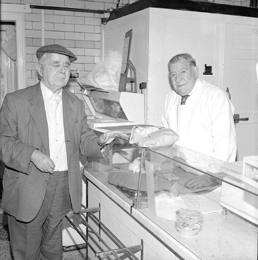 Mr Harry Harris, of H&W Harris, Butchers, 108, Croft Road, Stockingford,  serving Mr. Frederick Brown, aged 79,  of 40, Tomkinson Road, Nuneaton, in his shop.  1979 |  IMAGE LOCATION: (Warwickshire County Record Office) PEOPLE IN PHOTO: Harris, Harry, Brown, Frederick