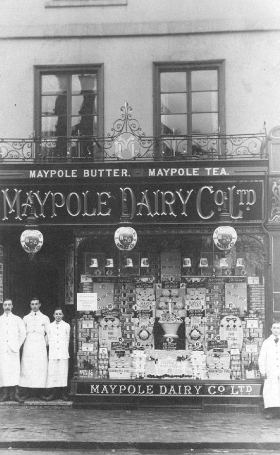 Bedworth Market Place. Maypole Dairy Co. Ltd. shop front with shop workers standing outside.  1910s |  IMAGE LOCATION: (Warwickshire County Record Office)