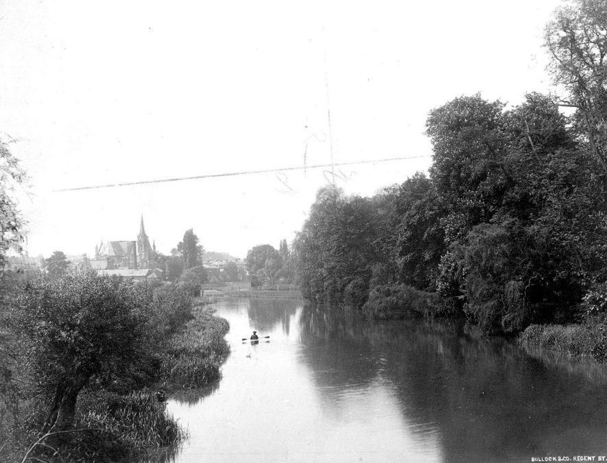 The River Leam at Leamington Spa.  1920s [It has been pointed out that this cannot be the 1920's. The Parish Church, left, is lacking its present tower(completed in 1902; there is no sign of the Mill suspension bridge(opened in 1903); the long roof below the church can only be Leamington Mill, the chimney can just be made out on screen. This was all demolished in 1899. The view is from the Willes Bridge. The dense overhanging foliage was encouraged in order to block views of the Mill from Jephsons gardens] |  IMAGE LOCATION: (Leamington Library)