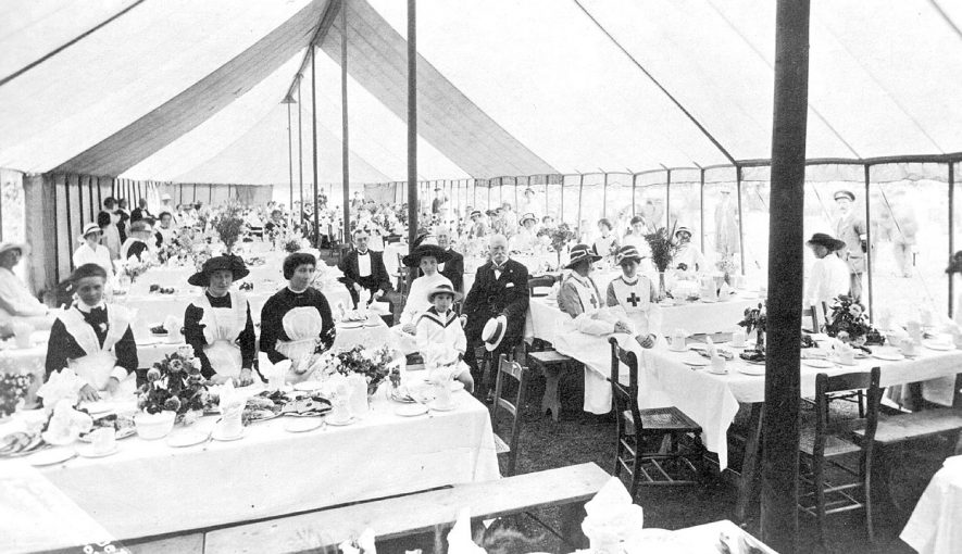 Large marquee with people seated at tables celebrating at an unknown occasion in Jephson Gardens, Leamington Spa.  July 1915    IMAGE LOCATION: (Leamington Library)