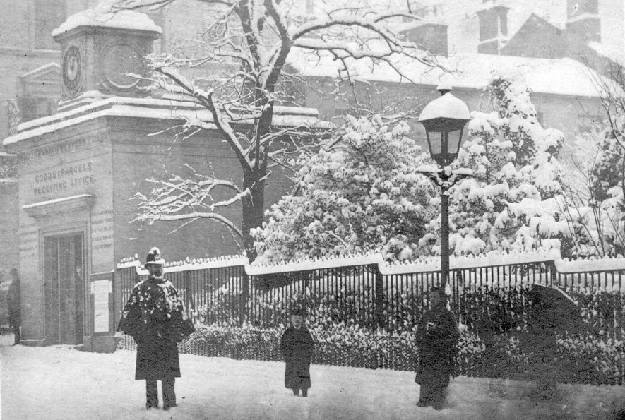 A policeman and children standing in the snow outside the good and parcels office [on the corner of the Parade and Regent Street East] in Leamington Spa.  1879 |  IMAGE LOCATION: (Leamington Library)