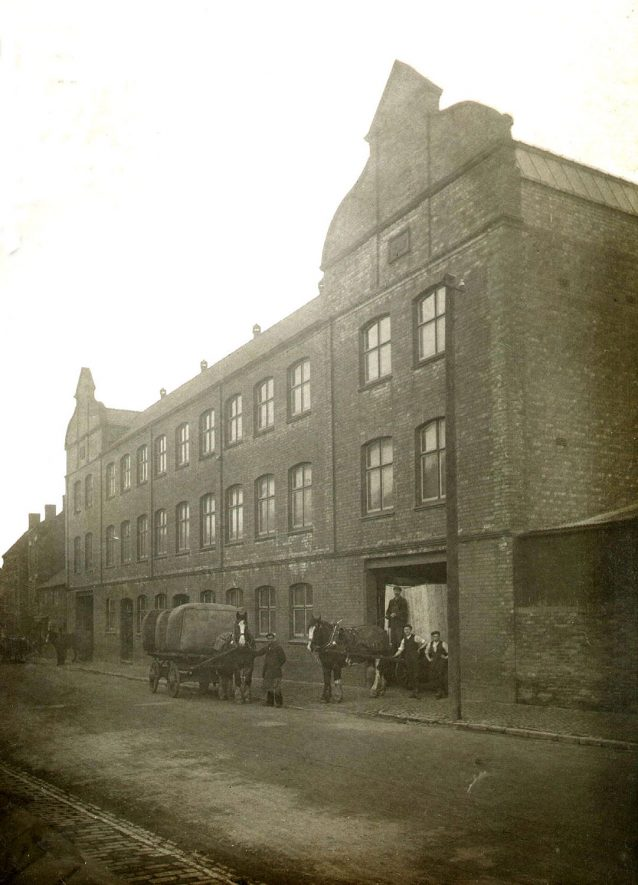 Outside view of Luckham and Pickering, hat factory with horse drawn delivery vans and a few workers.  1900s |  IMAGE LOCATION: (Warwickshire County Record Office)