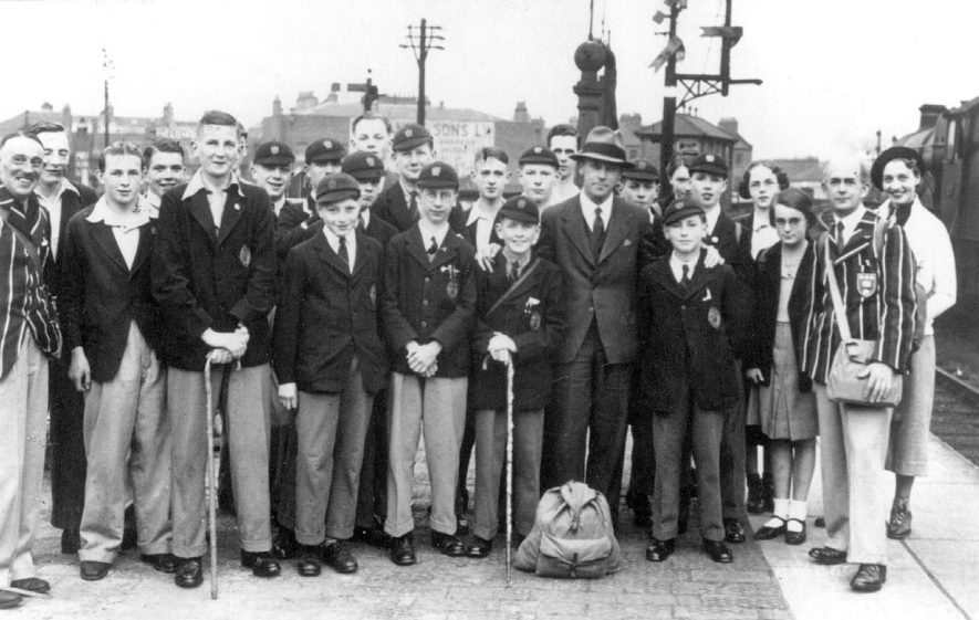 Party of boys and teachers from Leamington Spa College at G.W.R. Railway Station at start of holiday in Germany.  Teachers in school blazers: Capt. W.E. Foss (teacher of German) at left, O. Bentley, at right.  Two named boys: Peter Hewitt and Alec G. Robbins.  1932 |  IMAGE LOCATION: (Leamington Library) PEOPLE IN PHOTO: Robbins, Alec G, Hewitt, Peter, Foss, Capt W E, Bentley, O