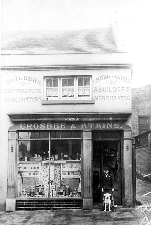 Crosbee & Atkins, Builders merchants and contractors, The Saltisford, Warwick.  Shop window with display of goods.  Boy with dog in doorway.  1930s