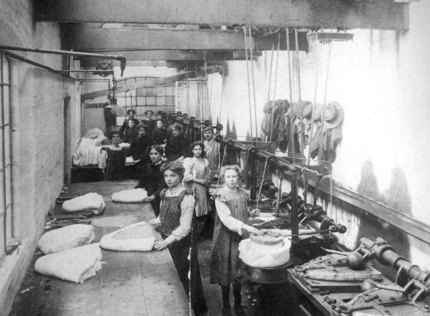 Interior of Luckham & Pickering's hat factory in Leicester Street, Bedworth, showing factory girls at their benches, and some of the machinery they used.  1900s |  IMAGE LOCATION: (Warwickshire County Record Office)
