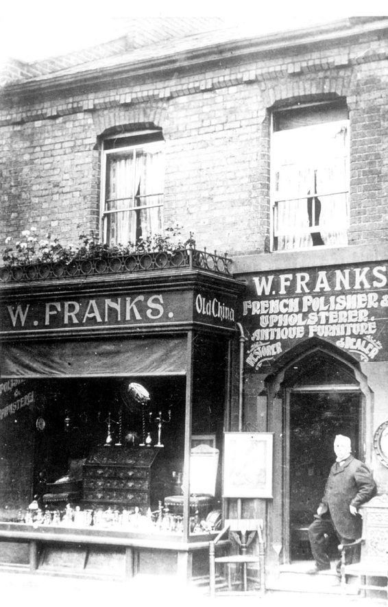 The Dell, Leamington Spa. Shop front of W. Franks, French polisher, upholsterer and dealer in antiques. Proprietor in doorway.  1900s |  IMAGE LOCATION: (Leamington Library) PEOPLE IN PHOTO: Franks, W