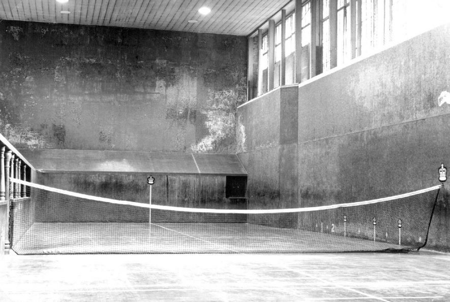The Royal (real) Tennis court in Bedford Street, Leamington Spa. Three of the courts high plastered walls are flanked with a sloping penthouse and the server has to defend a long netted opening called the Dedans. The  galleries, tambour and grille are features common to all courts - in the earliest days of the game these features may have been cloisters, a buttress and a serving hatch. On the floor are painted lines, a yard apart, called chases.  1987 |  IMAGE LOCATION: (Leamington Library)