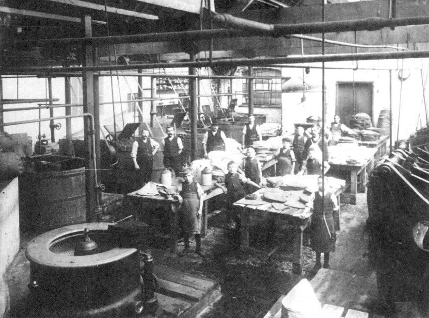 Interior of Luckham & Pickering's hat factory showing young boy workers with men and machinery, Bedworth.  1900s |  IMAGE LOCATION: (Warwickshire County Record Office)