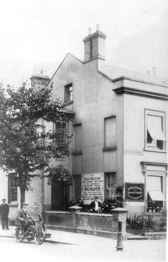 The business premises of R. Wallsgrove, decorator, supplier of baths, lavatories, and water closets and who undertook every description of sanitary work. He was also a gas and hot water fitter and supplier of wallpapers and artwork. No doubt the motor cycle combination was company transport and the three men employees. Clarendon Street, Leamington Spa.  1920s    IMAGE LOCATION: (Leamington Library)