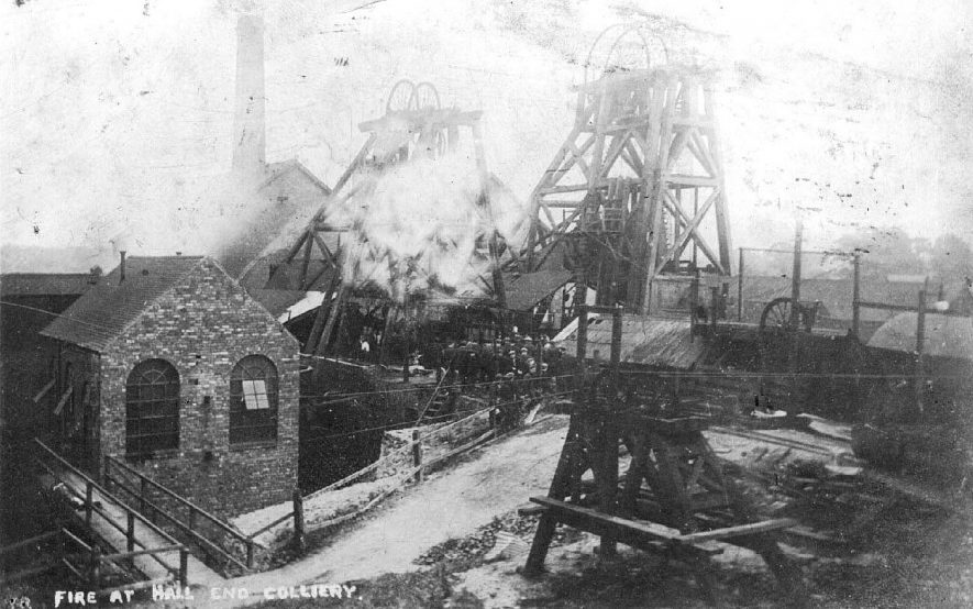 Hall End Colliery, Polesworth at the time of a fire.  Showing winding gear and mine buildings shrouded in smoke and a group of miners standing at a gate.  1900s |  IMAGE LOCATION: (Warwickshire County Record Office)