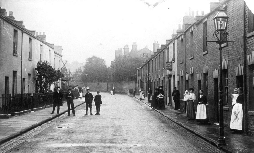 Terraced houses in King Street, Leamington Spa, with men, women and children standing in front of the houses and in the street. X marks Grandmother Smith holding George Selwyn Davies.  1909 |  IMAGE LOCATION: (Leamington Library) PEOPLE IN PHOTO: Smith as a surname, Davies, George Selwyn