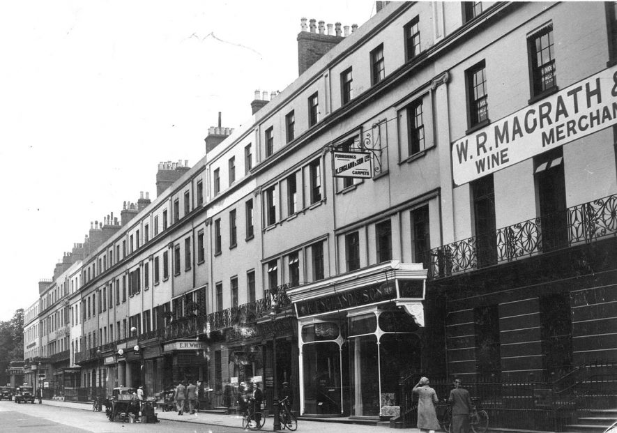 Shops in the Upper Parade showing W.R. Magrath, wine merchants; and K. England & Sons, furnishers.  1920s    IMAGE LOCATION: (Leamington Library)