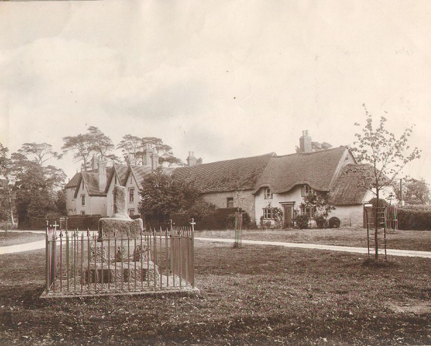 The Green at Bilton showing the Manor House.  The thatched cottage on the right is described as 'Arthur Law's cottage'.   The base of the Cross was re-set in 1897.  c.1900 |  IMAGE LOCATION: (Rugby Library) IMAGE DATE: (c.1900)