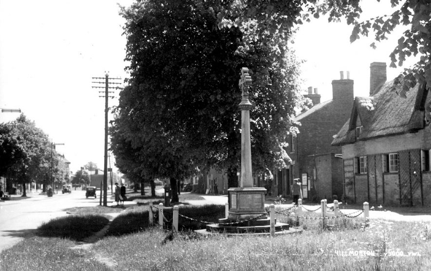 Hillmorton High Street showing the War memorial. 1930s[The first of the terrace cottages, just passed the thatched building on the right was the Village Hall and behind it was a cobbled courtyard surrounded by alms houses. There was a Water pump on the village green, just out of sight near the third tree visible in the centre of the picture. There was also a small blacksmiths shop down the lane behind the War Memorial.] |  IMAGE LOCATION: (Rugby Library)