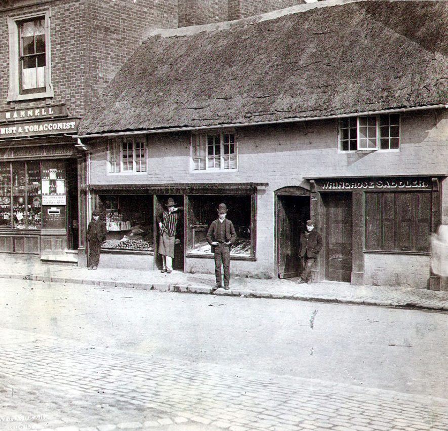 Shops in Church Street, Rugby: Wringrose, saddler, Hannel, chemist and tobacconist. Savings bank box set into shop doorway.   Thatch on one building.  Two men and two boys by shop windows.  1874 |  IMAGE LOCATION: (Rugby Library)