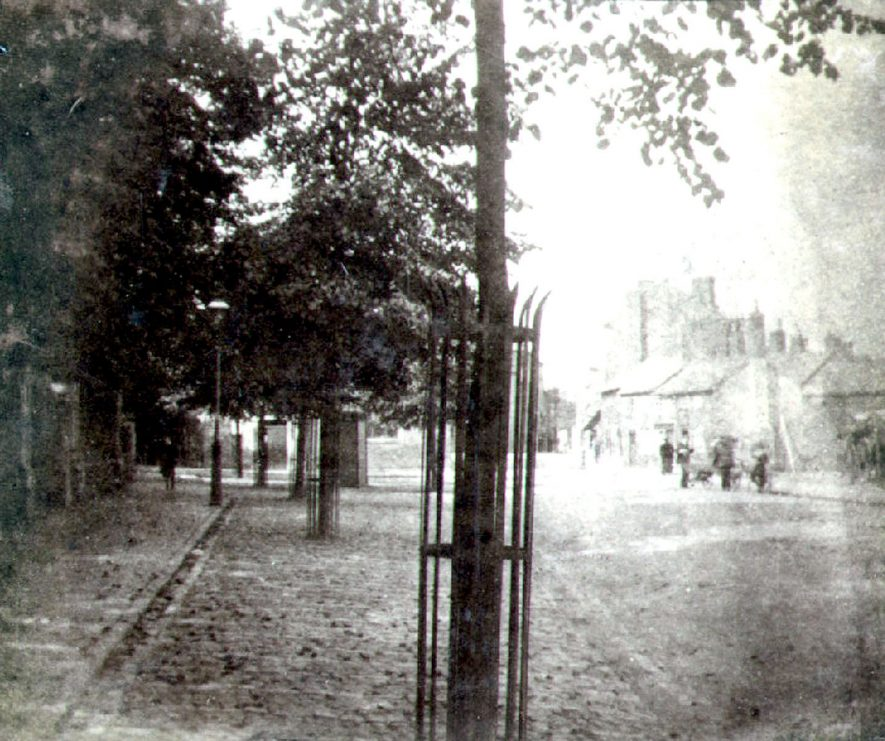 Church Street, Rugby.  Trees in iron tree guards.  Distant houses and people.  1910s |  IMAGE LOCATION: (Rugby Library)