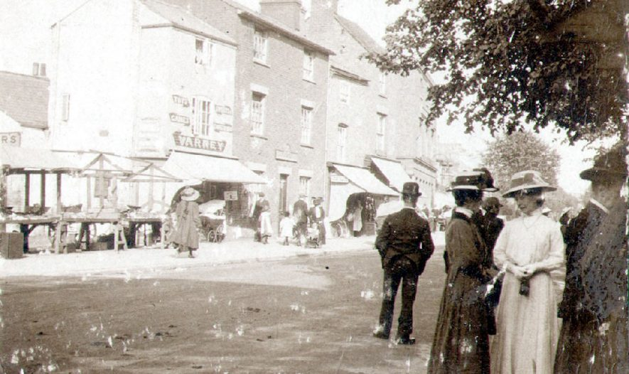 Church Street, Rugby.  Varney's shop, other shops and empty market stalls.  1910s