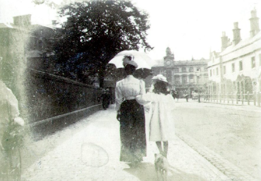 Church Street, Rugby, looking toward market place clock tower.  Iron railings fencing Church.  Woman and girl walking.  1890s |  IMAGE LOCATION: (Rugby Library)