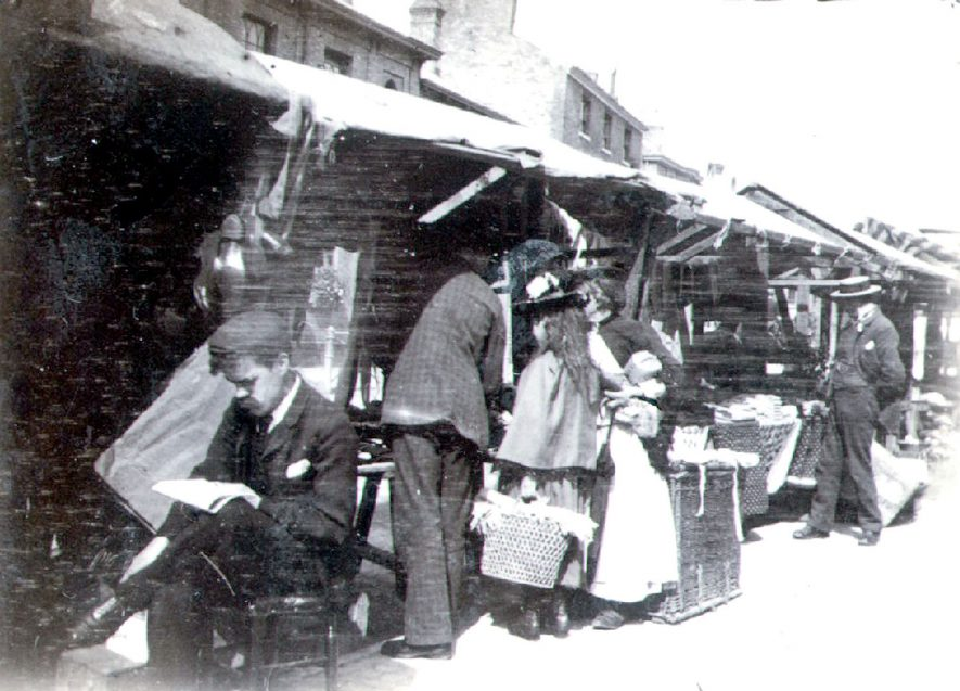 Market stalls in Church Street with customers, Rugby.  1890s |  IMAGE LOCATION: (Rugby Library)