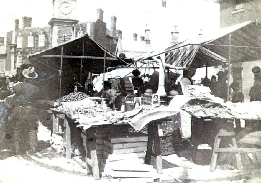 Market Stall in Church Street laid out with goods, Rugby.  Stall holders and customers.  1890s |  IMAGE LOCATION: (Rugby Library)
