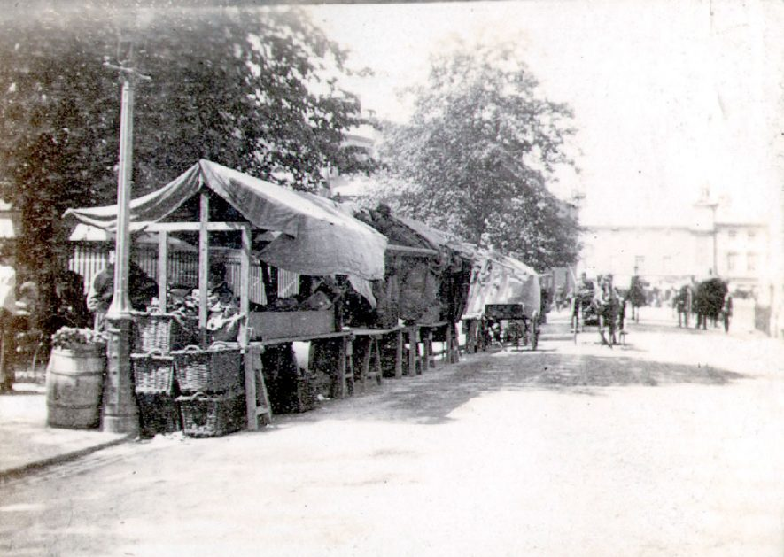 Market stall in Church Street, Rugby.  Horses and carriages in distance.  1890s |  IMAGE LOCATION: (Rugby Library)