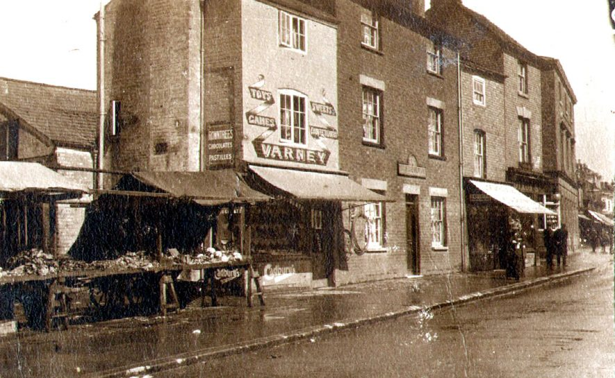 Church Street, showing Varney's shop and market stalls, Rugby.  1910s |  IMAGE LOCATION: (Rugby Library)