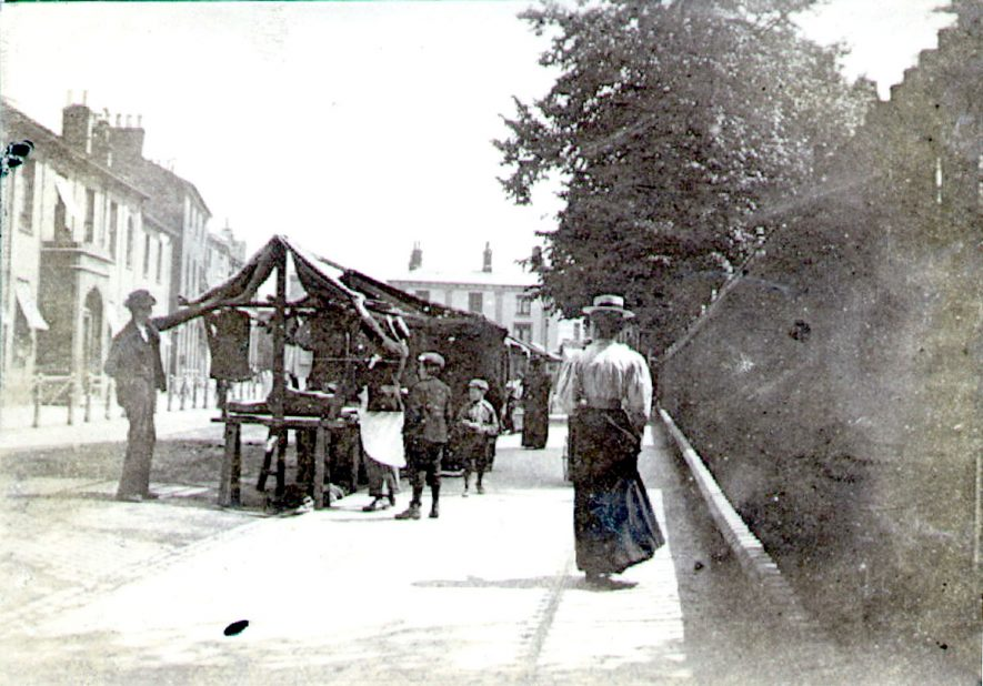 Church Street, Rugby.  Market stalls, stall-holders, children, lady passing by.  1900s 1900s. |  IMAGE LOCATION: (Rugby Library)
