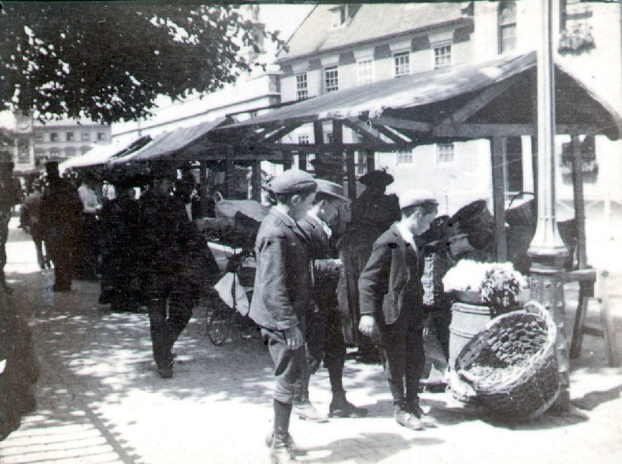 Market stall in Church Street, Rugby.  Boys examining goods in basket.  1890s |  IMAGE LOCATION: (Rugby Library)