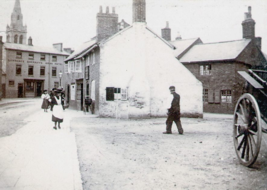 View of backstreets including hotel and St Andrew's Church spire in the background, Rugby.[The road on the left is Church Street, one of the main streets, the building in the centre of theimage is the Squirrel Inn.The hotel at the far end of Church Street is the Lawrence Sherriffs Arms Hotel.In 2010 the hotel is known as the Midas Lounge and the inn is known as The Squirrel.]  1890s |  IMAGE LOCATION: (Rugby Library)