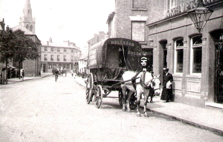 View of St Andrew's Church spire from Church Street, Rugby.   Horse and carrier's cart, lady on pavement.  1900s |  IMAGE LOCATION: (Rugby Library)