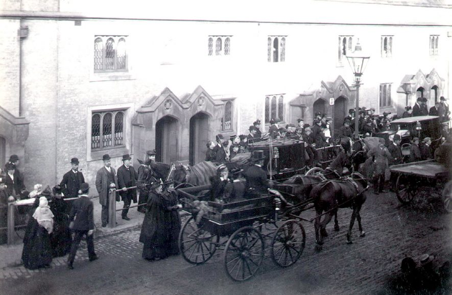 Funeral procession starting out from Lawrence Sheriff Almshouses in Church Street, Rugby.  Mourners and bystanders, horsedrawn vehicles.  1900 |  IMAGE LOCATION: (Rugby Library)