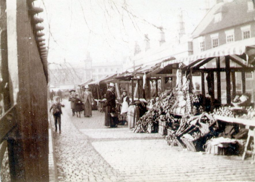 Market stalls with goods in Church Street, Rugby.  Families shopping.  1900s    IMAGE LOCATION: (Rugby Library)