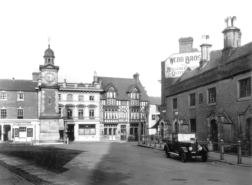 Rugby Market Place and Church Street.  Market clock.  Lawrence Sheriff Almshouse at  r. One parked car.  1935 |  IMAGE LOCATION: (Rugby Library)