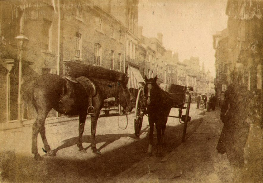 Horses and carts standing in High Street, Rugby.  1900 |  IMAGE LOCATION: (Rugby Library)