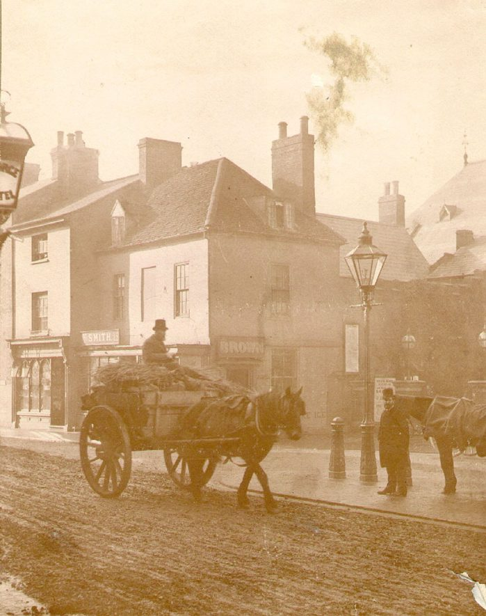 A hose and cart move through Market Place, Rugby.  1870 |  IMAGE LOCATION: (Rugby Library)